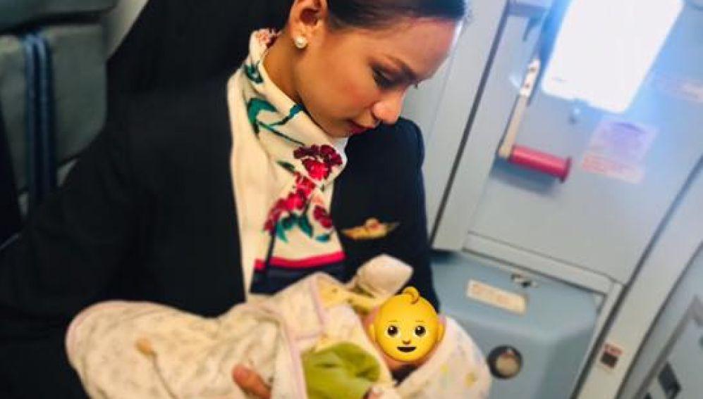 Una azafata de vuelo amamantando a un bebé