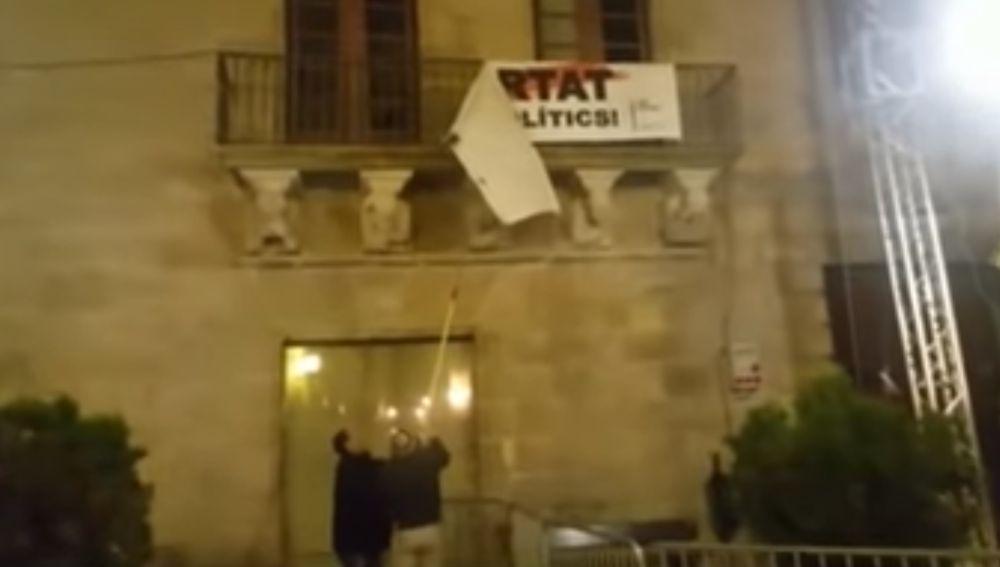 Dos personas descuelgan la pancarta por los políticos presos del balcón del Ayuntamiento de Cervera