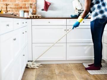 Una mujer friega el suelo de la cocina de su casa