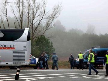 Varios viajeros suben a un autocar tras el descarrilamiento de un tren de cercanías