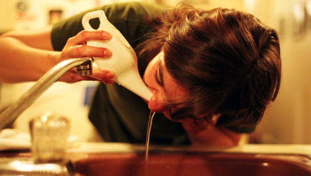 Una mujer lavándose la nariz con una 'Neti Pot', vasija especial para ello