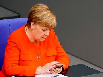 Fotografía de archivo que muestra a la canciller alemana, Angela Merkel, mientras utiliza su teléfono móvil