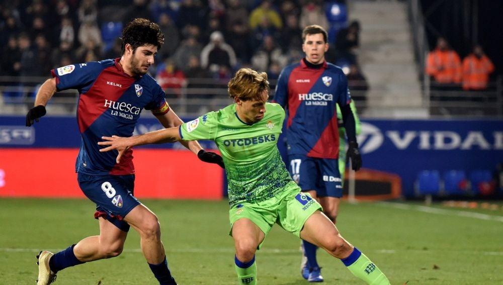 Canales intenta proteger el balón ante la defensa del Huesca
