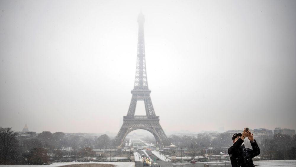 Un turista se toma una foto delante de la Torre Eiffel