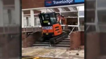 Un trabajador enfurecido estrella su excavadora contra la entrada de un hotel