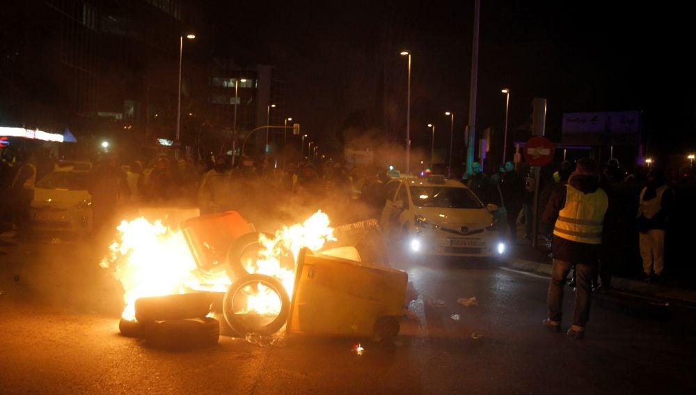 Taxistas queman contenedores en la entrada de IFEMA, en Madrid.