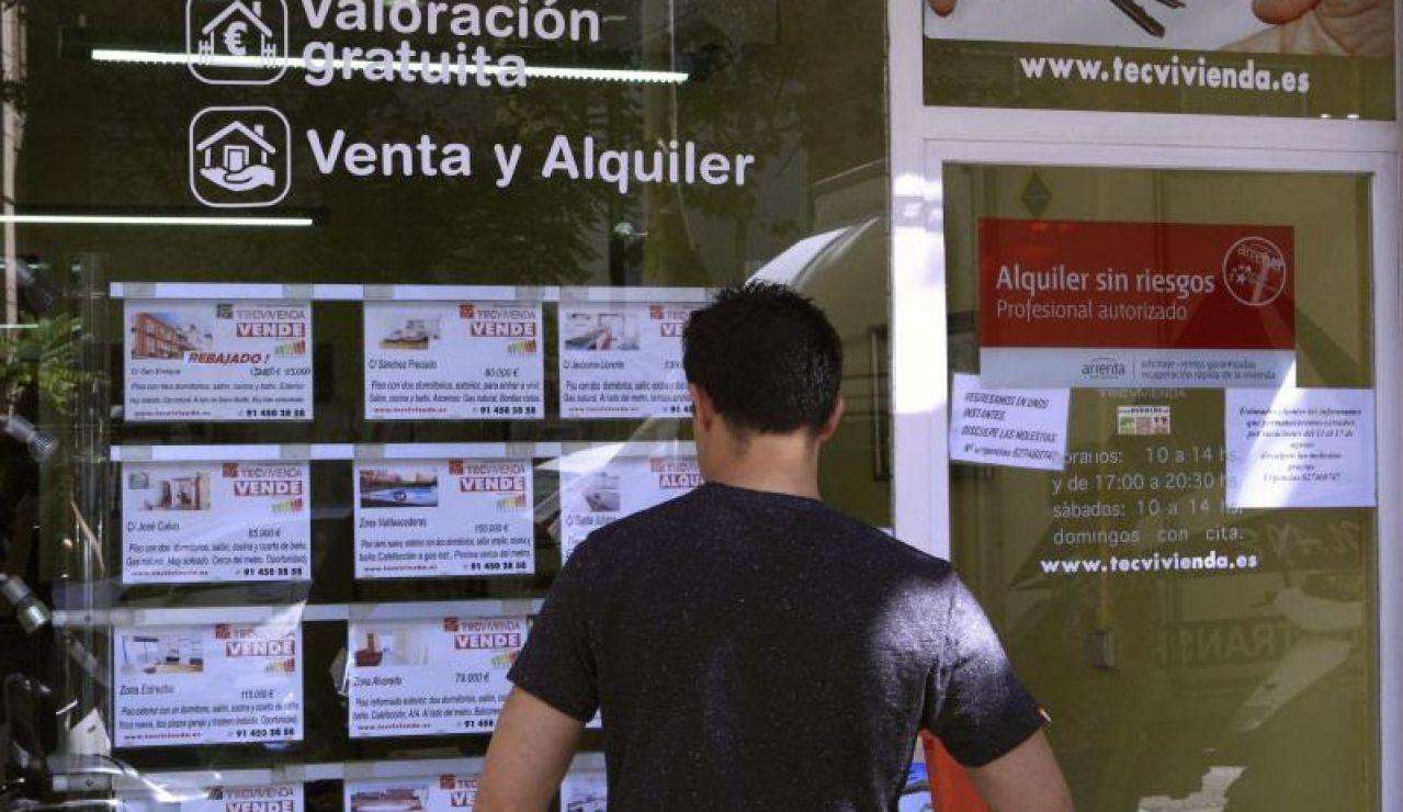 Imagen de archivo de un joven ojeando anuncios de pisos.