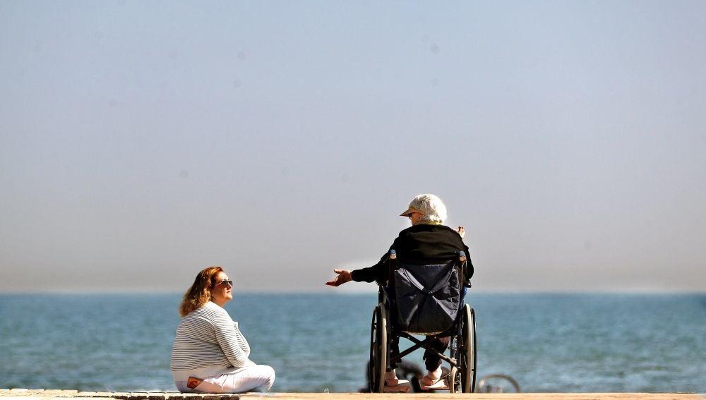 Dos mujeres conversan a orillas del mar mientras disfrutan del sol