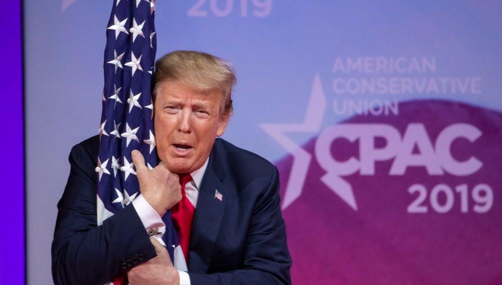 Donald Trump abrazando la bandera estadounidense