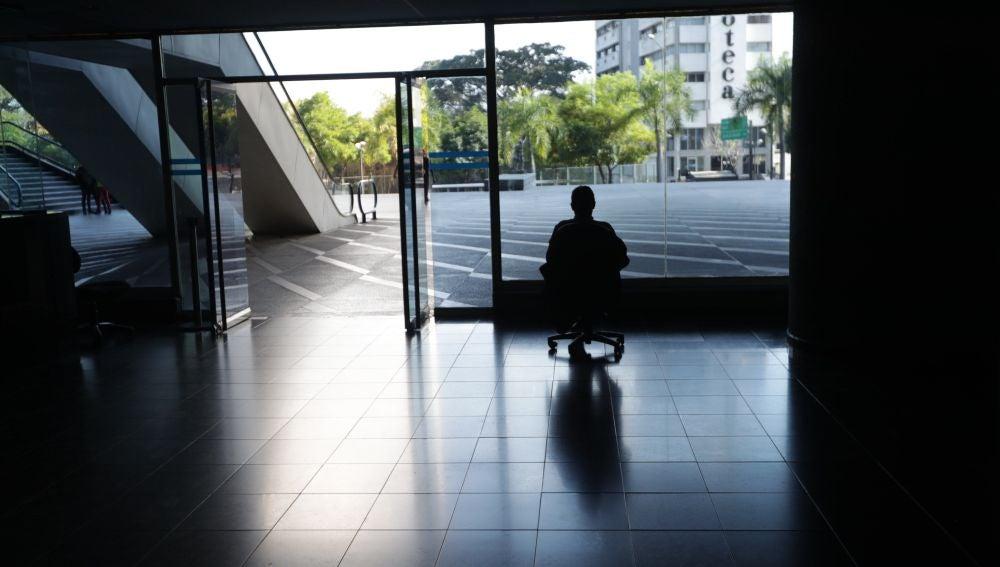 Un hombre mira por la ventana en una oficina sin luz en Caracas, Venezuela.