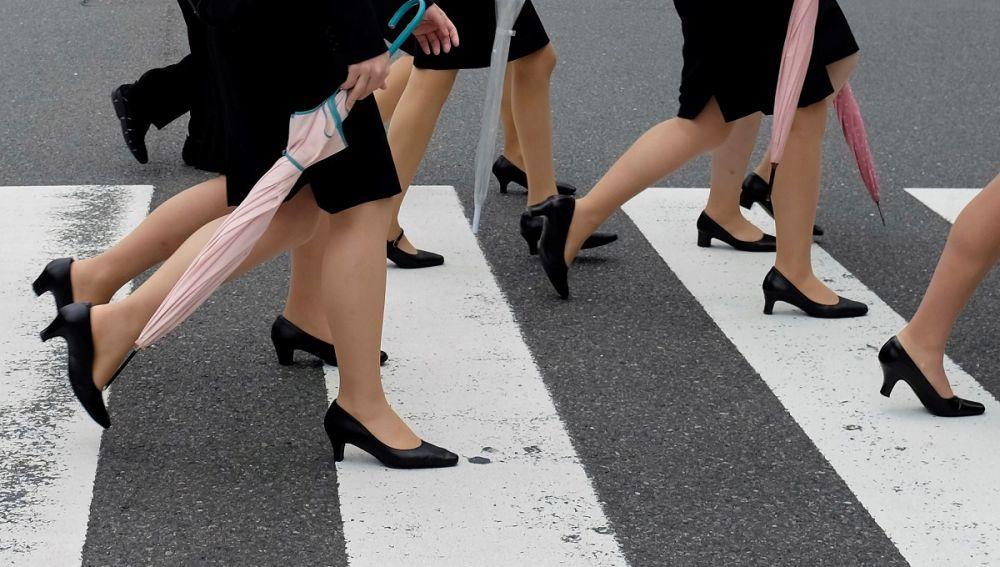 Varias mujeres cruzan un paso de cebra con tacones