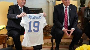 El presidente de EEUU, Donald Trump, recibe una camiseta la selección brasileña durante la reunión con Jair Bolsonaro