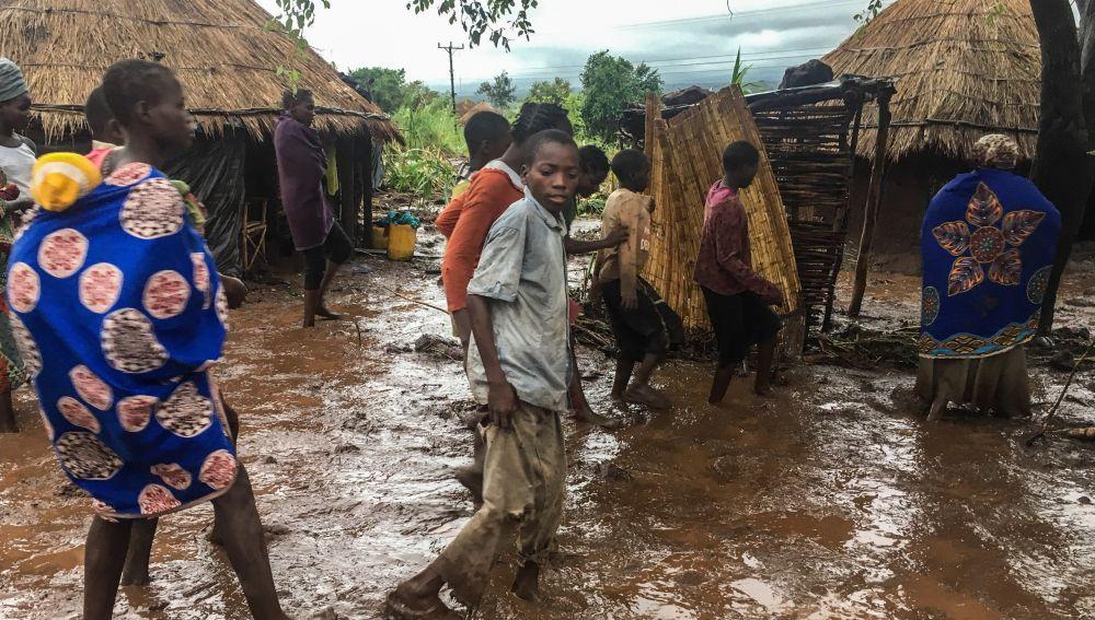 Habitantes de Chiluvi, una aldea del centro de Mozambique, caminan por una calle cubierta de lodo