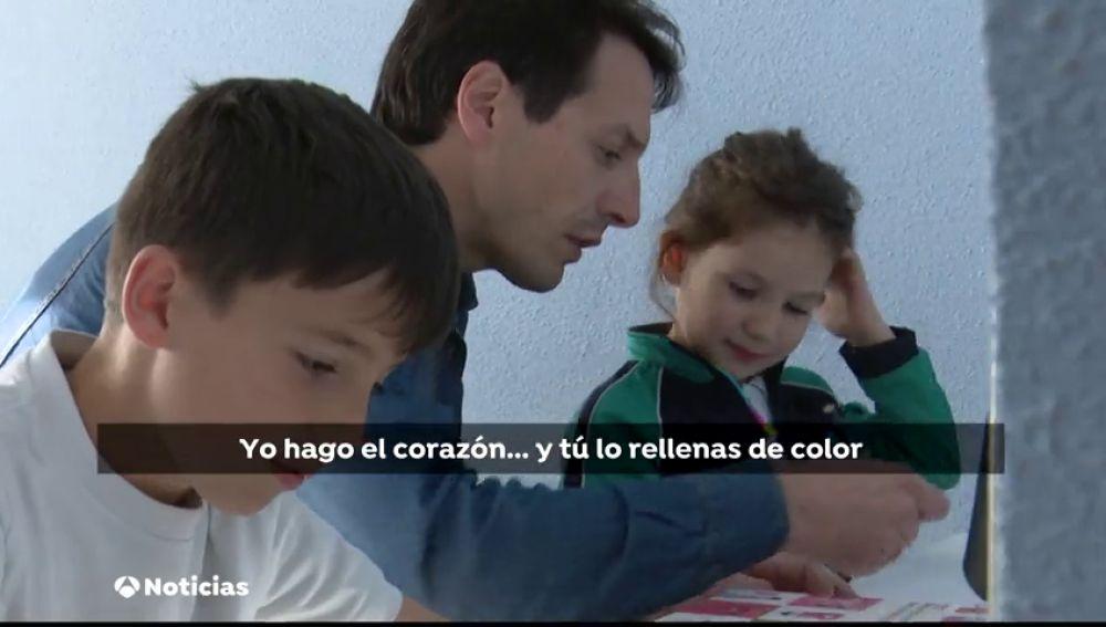 Un padre haciendo los deberes con sus hijos