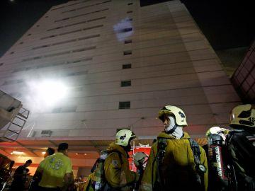 Miembros del cuerpo de bomberos asisten al lugar en el que se produjo un incendio
