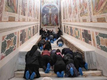 Varias personas recorren de rodillas la Escalera Santa