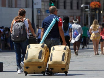 Varios turistas con sus maletas en las calles de Madrid