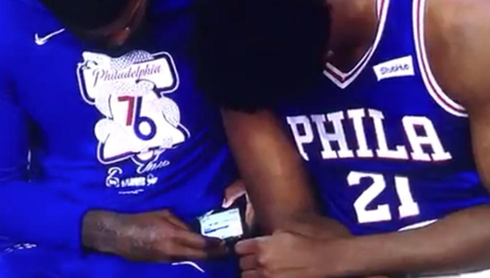 Amir Johnson y Joel Embiid miran el móvil durante el partido contra los Nets