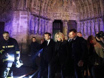 El presidente de Francia, Emmanuel Macron (c), y su esposa Brigitte Macron (c-d) visitan a los bomberos que intentan apagar el incendio en la catedral de Notre Dame