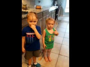 Un niño corta el pelo a su hermana y a él