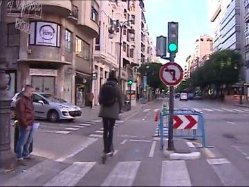 Un ciudadano circula por una calle en un patinete.