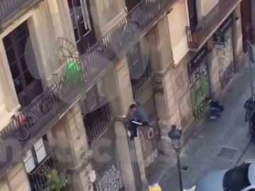 Un okupa trepando la fachada de una vivienda