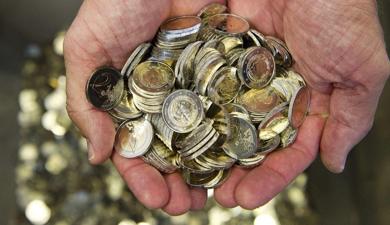Un hombre sostiene monedas de euro