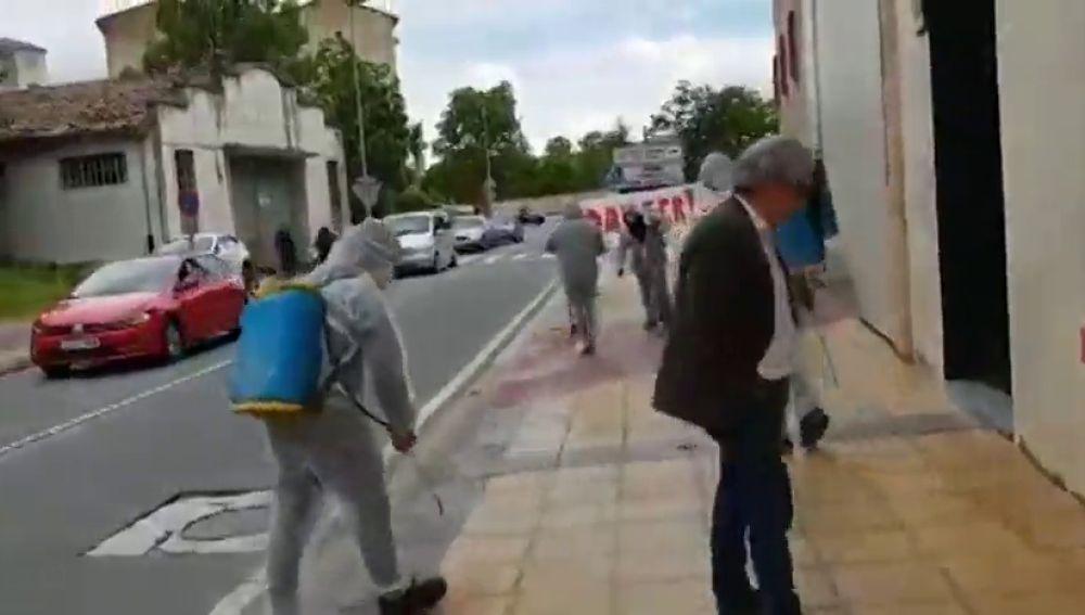 Decena de personas con trajes de fumigar limpian la calle tras pasar Rivera