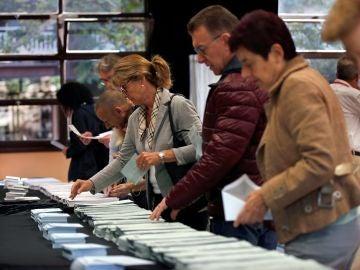 Varios ciudadanos escogen sus papeletas electorales en el Centre Cívic La Sedeta de Barcelona