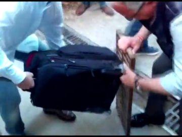 El candidato del PP a la alcaldía de Barcelona ayuda a una periodista a desencallar una maleta con ruedas de un desagüe