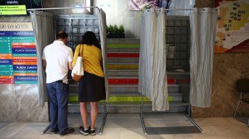 Dos personas eligen sus papeletas para votar en un colegio electoral