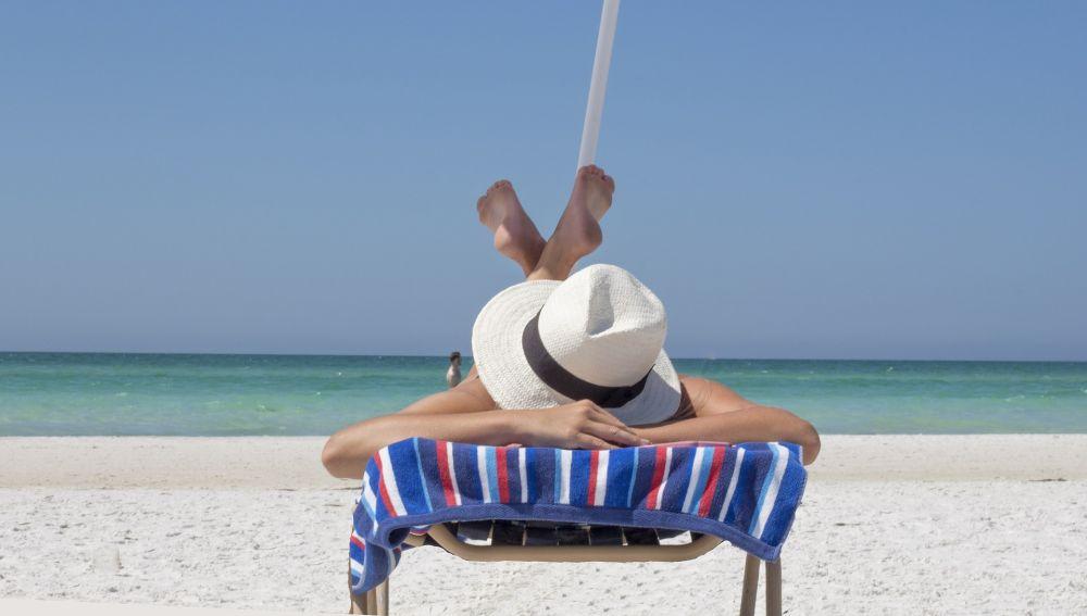 Una mujer toma el sol en una playa