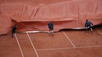 Los operarios de Roland Garros ponen la lona en la Philippe Chatrier