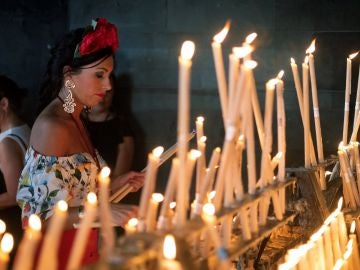 Una rociera coloca una vela en el Santuario de la Virgen del Rocío