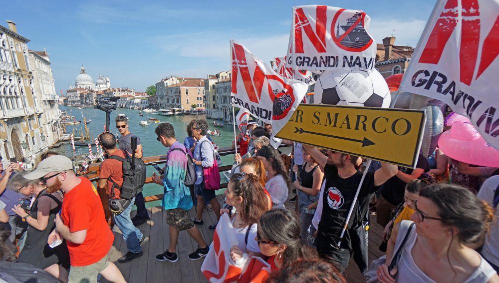 Varias personas marchan con banderas 'No Grandi Navi'