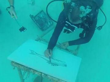 Un artista pintando bajo el agua