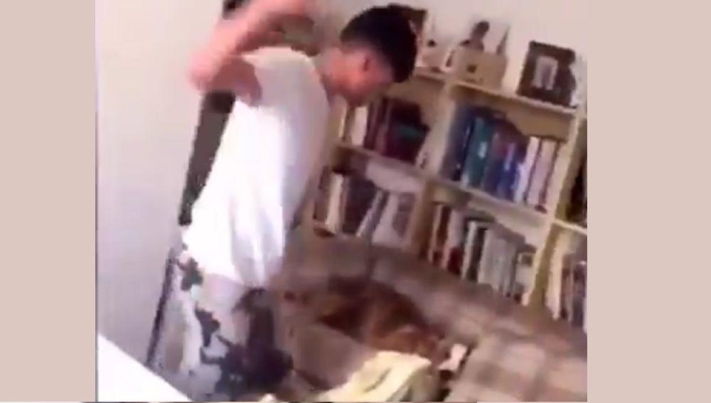 El joven golpeando al perro