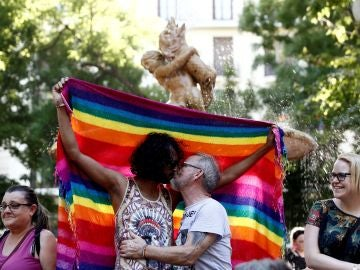 Dos hombres besándose ante la bandera del orgullo gay