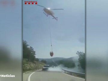 Los bomberos apagan un coche en llamas en medio de la carretera para evitar otro incendio forestal