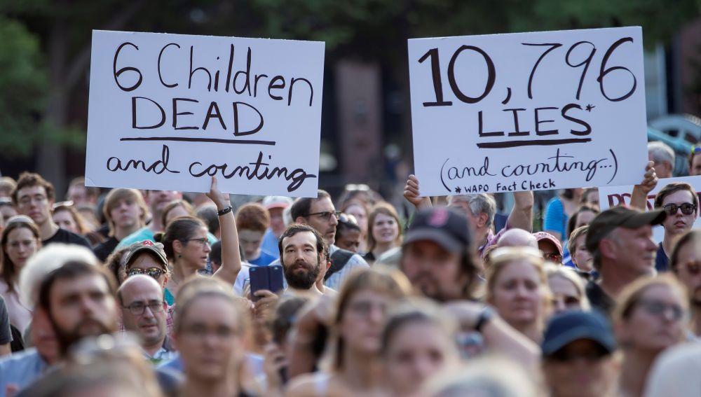 """Manifestantes sostienen carteles en los que se leen """"6 niños muertos y contando"""""""