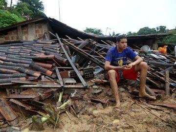 Un joven sobre los escombros de las inundaciones en Lima.