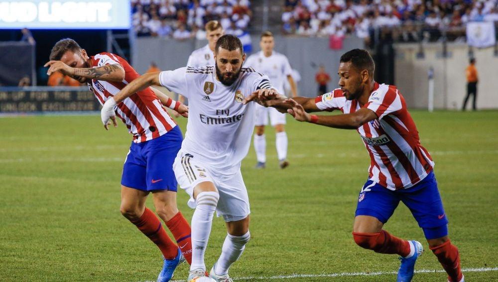 Karim Benzema pelea por el balón durante un partido contra el Atlético de Madrid
