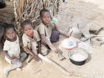Tres niños esperan al camión que les traerá el agua en África