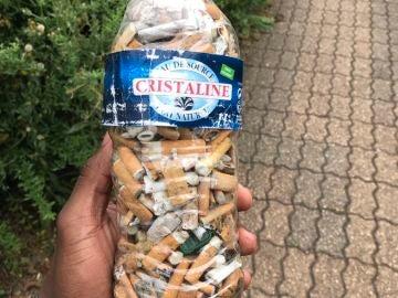 Una botella llena de colillas