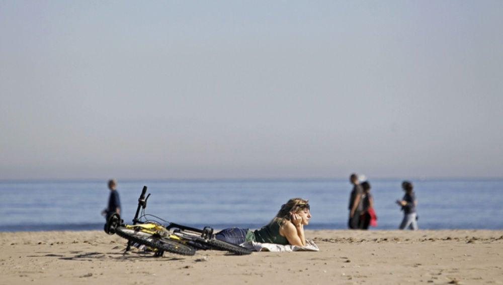 Una chica toma el sol en la Playa de la Malvarrosa (Valencia)