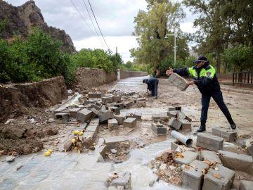 Policías locales de Blanca, Murcia, retiran los bloques de un muro derribado por las fuertes lluvias