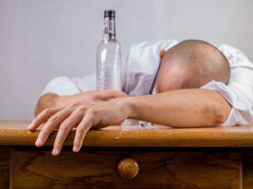 Un hombre borracho en la barra de un bar. Imagen de archivo