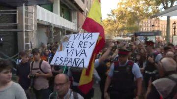 Los mossos escoltan a un ciudadano con la bandera de España en la manifestación de los estudiantes