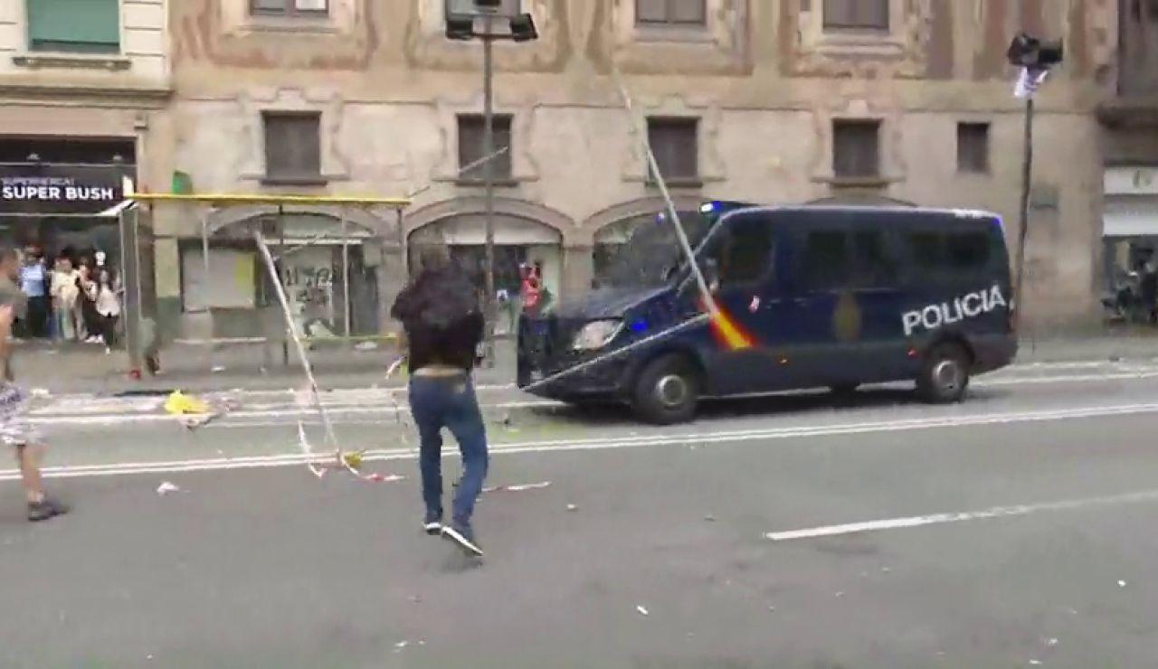 Un grupo de manifestantes lanzan pintura y todo tipo de objetos a la Policía en la huelga independentista