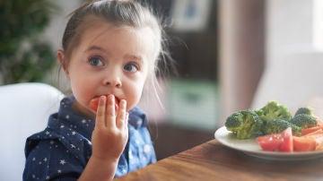 Niña comiendo vegetales